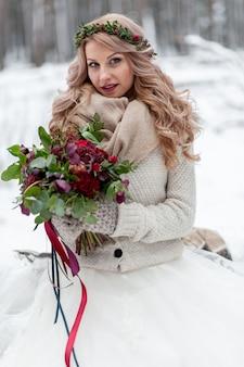 Una giovane ragazza di aspetto slavo con una corona di fiori di campo. la bella sposa bionda tiene un mazzo nel fondo dell'inverno.