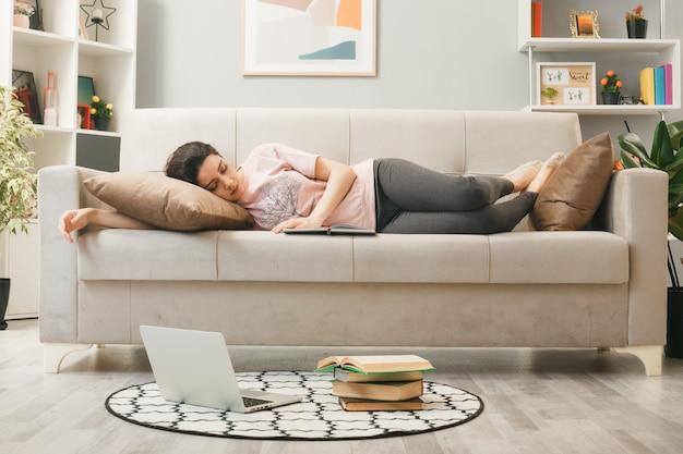 Giovane ragazza sul divano con taccuino in soggiorno