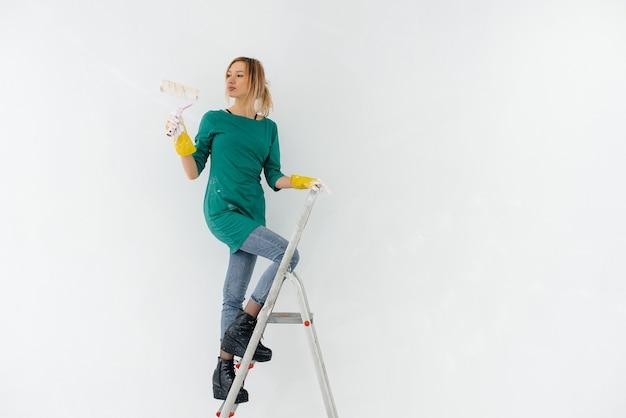 Una giovane ragazza sulle scale dipinge un muro bianco con un rullo. riparazione degli interni.