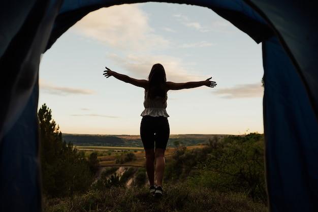 Giovane ragazza in piedi sul bordo della scogliera con le mani alzate e godersi il paesaggio della natura.