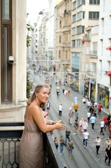 La ragazza sta sul balcone contro lo sfondo della via istiklal a istanbul turchia