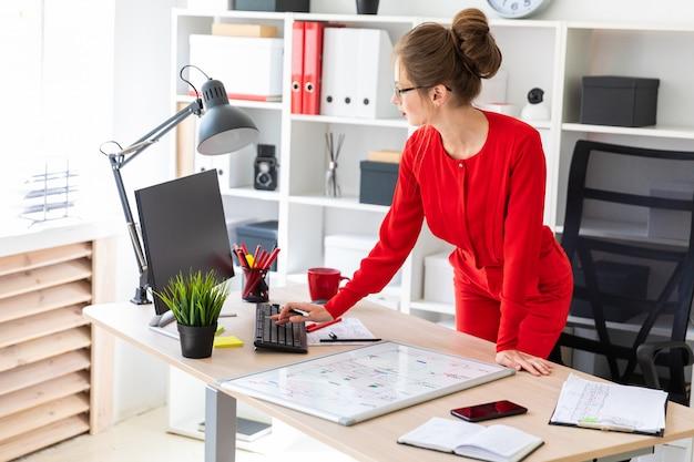 Una ragazza si trova vicino alla scrivania in ufficio e lavora con un computer, un pennarello e una lavagna magnetica.