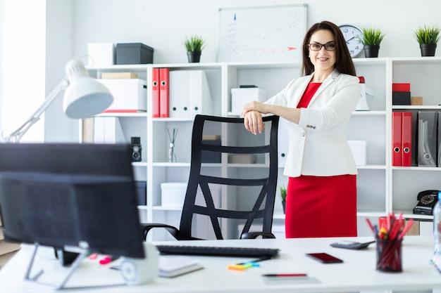 Una ragazza si trova in ufficio vicino a una sedia con la schiena alta.
