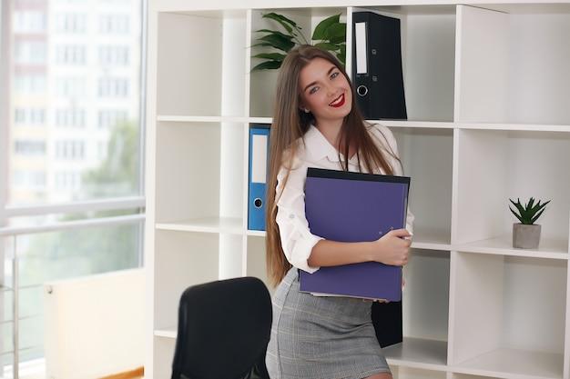 Una giovane ragazza è in piedi sullo scaffale e tiene una cartella rossa.