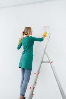 Una giovane ragazza su una scala a pioli dipinge un muro bianco con un rullo. riparazione degli interni.