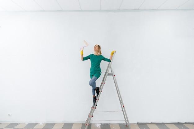 Una giovane ragazza su una scala a pioli dipinge un muro bianco con un rullo