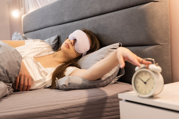 Giovane ragazza che ferma la sveglia mentre è sdraiata sul letto di casa. la bella donna indossa la benda sugli occhi. mattina per svegliarsi. interno della camera da letto in appartamento moderno