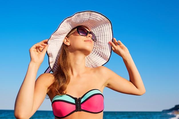 Una giovane ragazza con cappello a strisce e occhiali da sole sullo sfondo del cielo e della spiaggia del mare in vacanza durante un viaggio