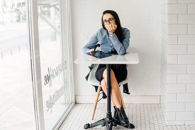 Una giovane studentessa in camicia blu e occhiali si siede in un caffè e guarda pensieroso in un caffè