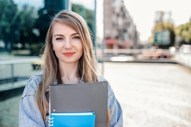Studentessa in possesso di una cartella del taccuino nelle sue mani e in piedi sulla strada