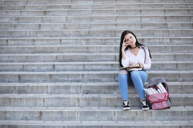Giovane studentessa per strada con uno zaino e libri
