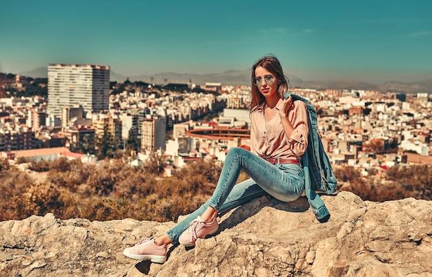 Una giovane ragazza in occhiali da sole, vestita in jeans e una maglietta si siede su una roccia, vista posteriore della città costiera.