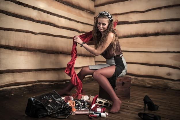 Una giovane ragazza prende una sciarpa rossa da una pila di accessori che giace sul pavimento in una stanza con pareti in legno. il concetto di cose superflue e accessori femminili necessari