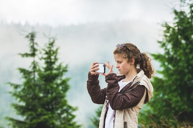 Ragazza che cattura immagini delle montagne