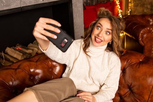 Ragazza che prende selfie con lo smartphone alla vigilia di natale. lei seduta sulla poltrona e mostrando la sua lingua.