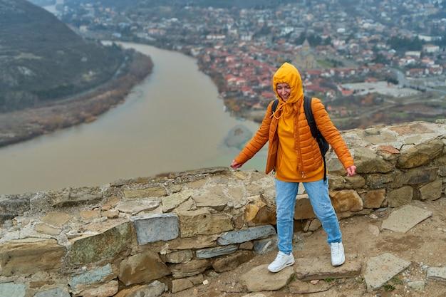 Il turista della ragazza gioisce posando contro un paesaggio naturale stupefacente. la confluenza di due fiumi nella città di mtskheta in georgia.