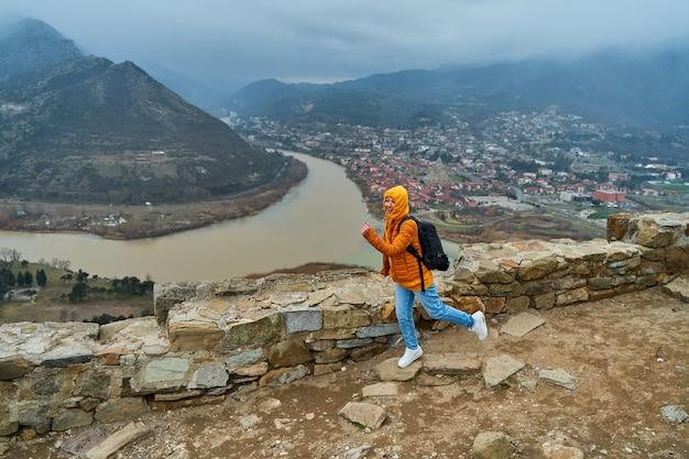 Turista giovane ragazza gioisce posa sullo sfondo di un incredibile paesaggio naturale. la confluenza di due fiumi nella città di mtskheta in georgia.