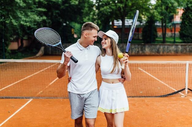 Ragazza giovane formazione con istruttore di tennis sul campo in terra battuta.