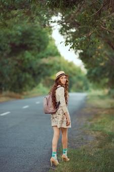 Viaggiatore giovane ragazza godersi il viaggio a piedi. donna felice che cammina con cappello e zaino sulla strada e che guarda l'obbiettivo.