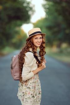 Viaggiatore giovane ragazza godersi il viaggio a piedi. ritratto di donna felice che cammina con cappello e zaino sulla strada e che guarda l'obbiettivo.