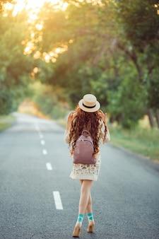 Il viaggiatore della ragazza gode del viaggio. donna felice che cammina sulla strada.