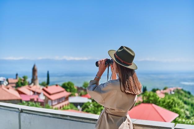 La giovane viaggiatrice guarda attraverso il binocolo durante il viaggio di vacanza in una luminosa giornata di sole