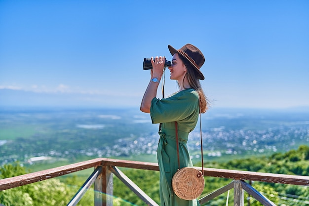 La giovane viaggiatrice che indossa il cappello guarda attraverso il binocolo durante il viaggio di fine settimana di vacanza in una luminosa giornata di sole
