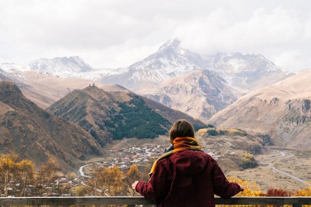 Una giovane ragazza viaggia, guarda le maestose montagne alte, gode della natura