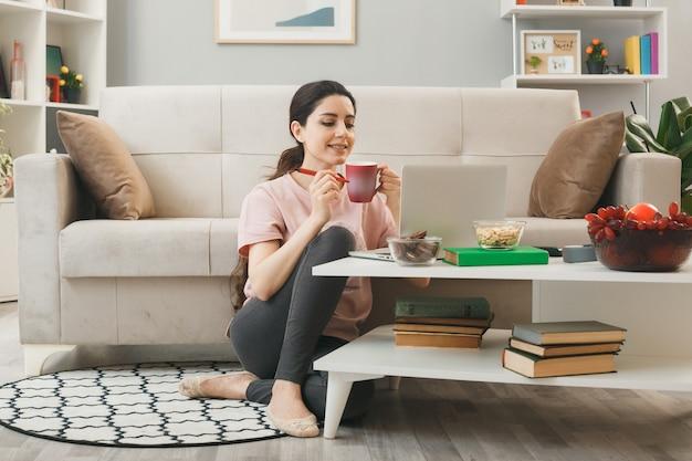 La ragazza ha usato il computer portatile che tiene la tazza di tè che si siede sul pavimento dietro il tavolino da caffè nel soggiorno