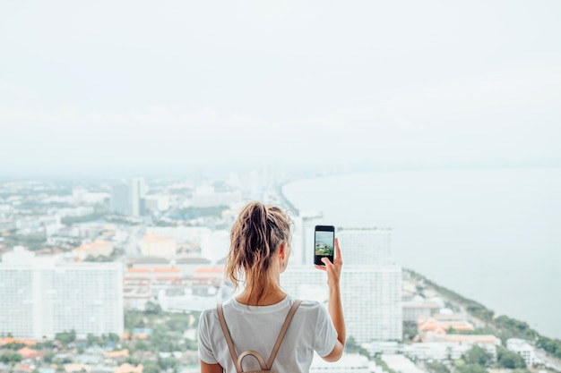 Ragazza che utilizza il telefono cellulare per scattare una foto della grande città fuori dalla finestra