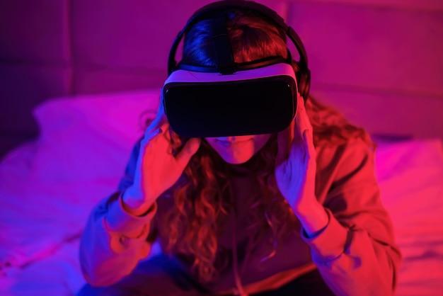 Giovane ragazza in occhiali per realtà virtuale con illuminazione blu e rossa nella stanza nel letto. intrattenimento a casa