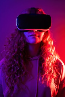 Giovane ragazza in occhiali per realtà virtuale con illuminazione blu e rossa nella stanza. intrattenimento a casa