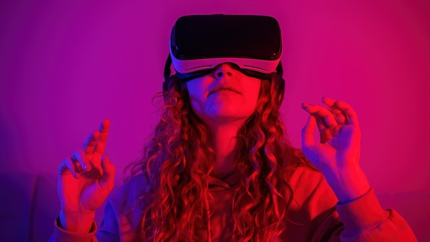 Giovane ragazza in occhiali per realtà virtuale con illuminazione blu e rossa nella stanza con le mani alzate. intrattenimento a casa