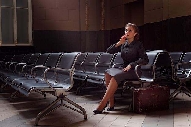 Giovane ragazza nella sala d'attesa della stazione ferroviaria con una valigia