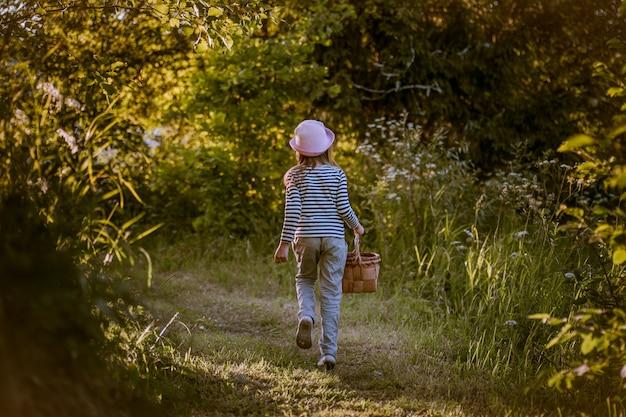 Ragazza che cammina su un sentiero attraverso boschi verdi che trasportano un cesto di corteccia di betulla