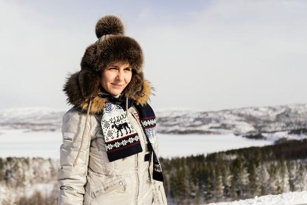 Una giovane ragazza in abiti caldi viaggia attraverso il freddo nord, ovunque la neve bianca