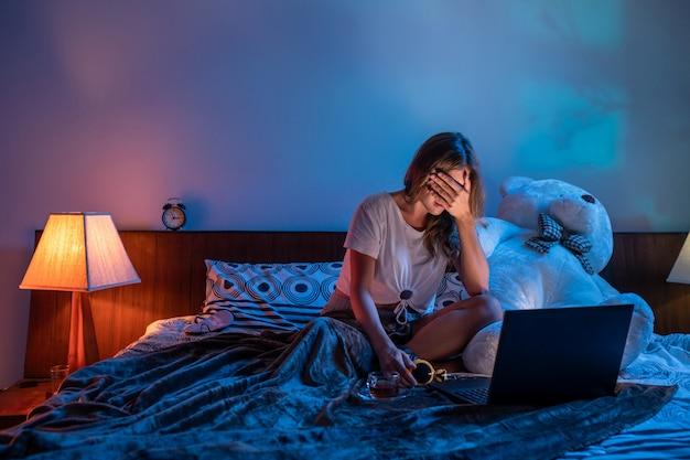 Ragazza che guarda un film horror sul suo computer portatile