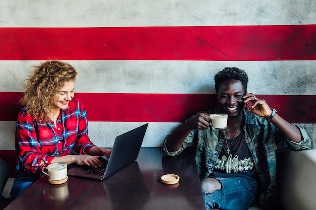Giovane ragazza che indossa una camicia casual al bar con un maschio africano nero, una tazza di caffè e un tablet.