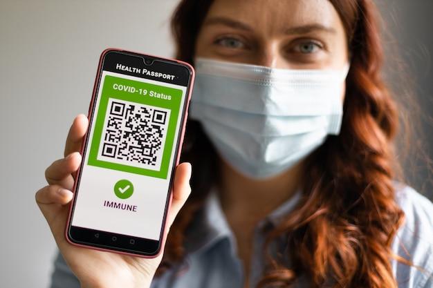 Giovane ragazza che indossa una maschera facciale in possesso di passaporto, biglietto e smartphone con app passaporto sanitario digitale per viaggiare durante la pandemia di covid-19.