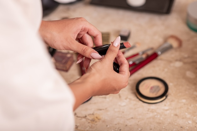 Una giovane ragazza in un accappatoio bianco in posa mentre si chiude il rossetto su uno sfondo di cosmetici sparsi.