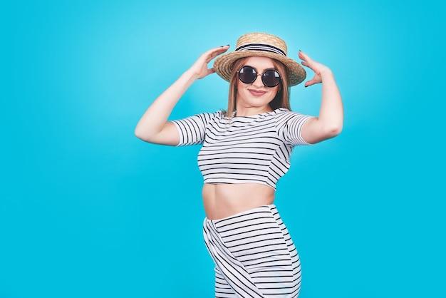 Giovane ragazza in strisce bianche e nere, cappello, occhiali da sole, bocca aperta emotivamente su uno sfondo blu brillante con un corpo perfetto. isolato. studio girato.