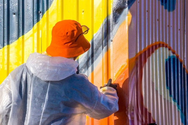 Una giovane ragazza in camice bianco con macchie di vernice dipinge graffiti di recinzione in ferro a coste