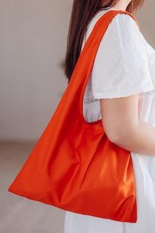Una giovane ragazza in abito bianco tiene una borsa della spesa di cotone arancione sulla spalla
