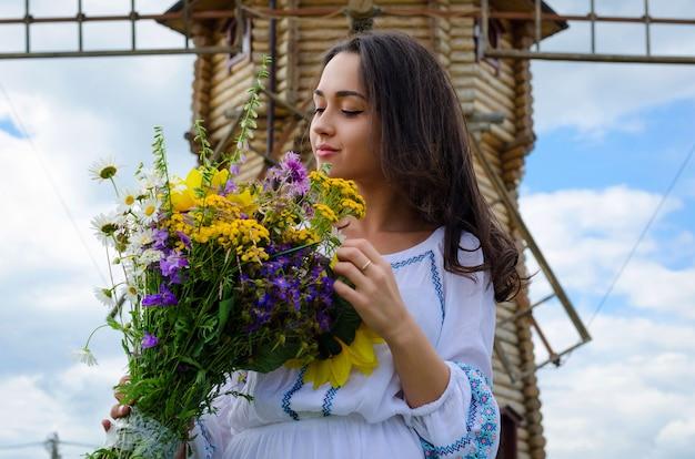 Una giovane ragazza in abito bianco vicino a un mulino a vento. ragazza in costume popolare e fiori selvatici
