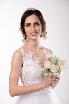 Ragazza in un vestito bianco con un bello mazzo, sposa felice emozionale su un fondo bianco.