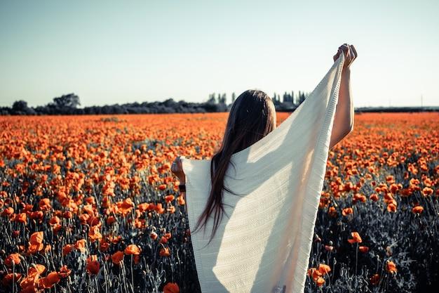 Una ragazza in bianco su un campo di papaveri, emozioni positive che sentono la vita, la pace della mente.