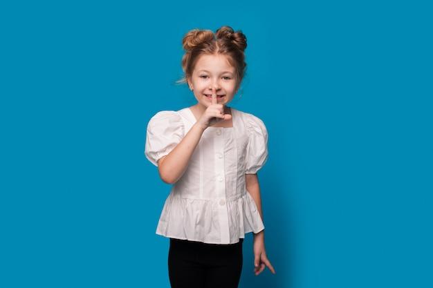 La ragazza in una camicia bianca sta gesticolando il segno di silenzio alla macchina fotografica che posa su una parete blu dello studio