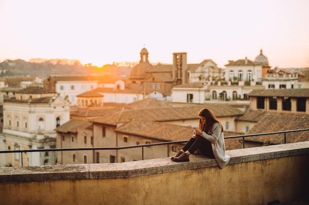 Ragazza che usa il suo telefono cellulare sul tetto durante il tramonto.