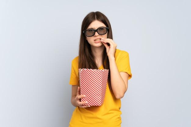Giovane ragazza con gli occhiali 3d e in possesso di un grande secchio di popcorn