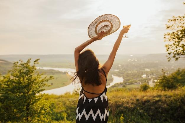Una giovane ragazza con i capelli neri è in piedi con la schiena su una collina con un vestito elegante e un cappello di paglia a guardare il tramonto, alzando le braccia verso l'alto.